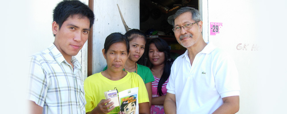 Station Manager Em Perez with a Gawad Kalinga family recipient of the Portable Missionary (PM) radio